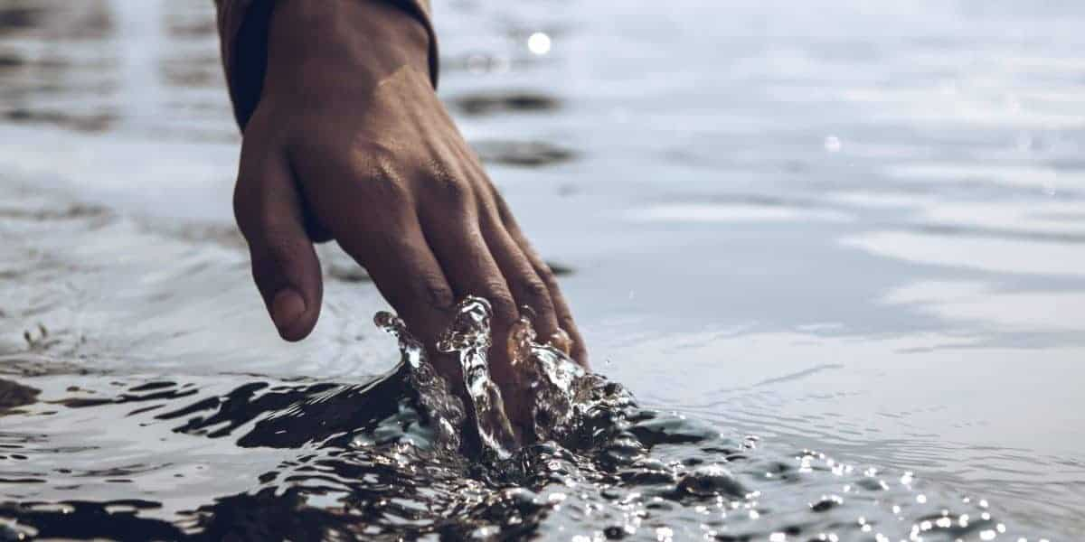 close up photo of a person s hand touching body of water scaled e1580734153501