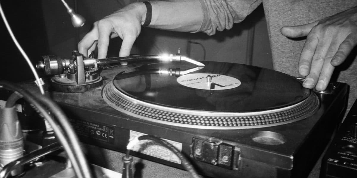 grayscale photo of person playing turntable scaled e1580733455540